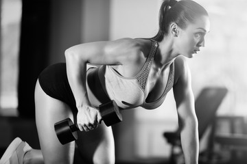 Young woman training with dumbbell in gym. Black and white photo