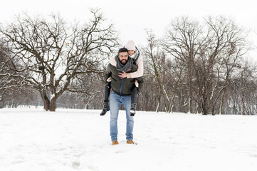 Loving couple enjoying the snow in the park