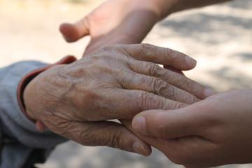 yaşlı kadın elini tutan genç kadın eli
