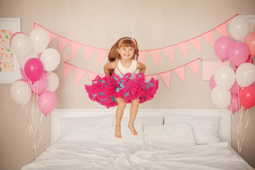 Cute girl jumping on bed in room decorated for birthday celebration