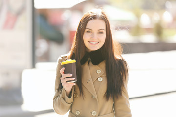 Beautiful young woman with cup of tasty coffee outdoors