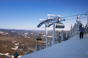Mountain ski resort, the view from the top of the slopes of the valley. Skiers on a steep slope. The mast for the ski lift. Winter sport.