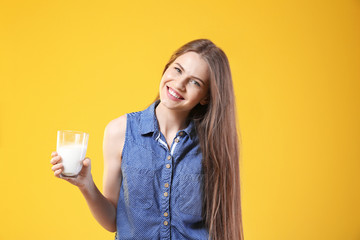 Beautiful young woman with glass of milk on yellow background
