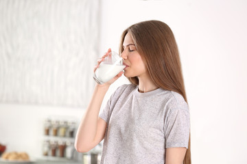 Beautiful young woman drinking milk at home