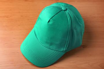 Green cap for branding on wooden background