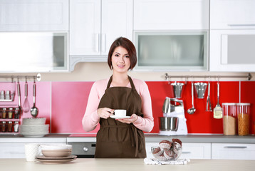 Young woman with cup of coffee on kitchen at home