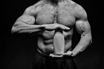 sexy muscular male torso of athlete man holds drink bottle