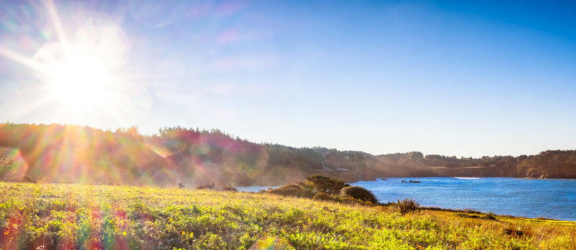 Sunrise on a coastal landscape by the Pacific Ocean. Lens flare and sun beams