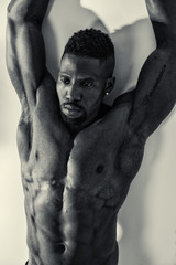 African American bodybuilder man, naked muscular torso, wearing jeans, leaning on white wall