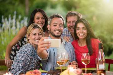 Friends taking a selfie on a terrace by a summer evening