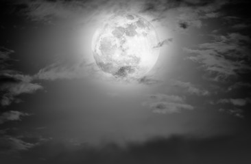 Nighttime sky with clouds and bright full moon.  Black and white