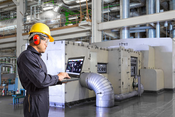 Engineer using laptop computer for maintenance in powerhouse