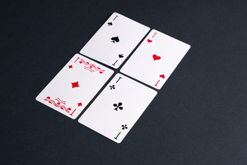 High Angle View of Four Playing Cards Spread Out on Dark Background Showing Aces from Each Suit - Hearts, Clubs, Spades and Diamonds