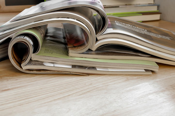 Closeup Stack of colorful magazines on wooden table .