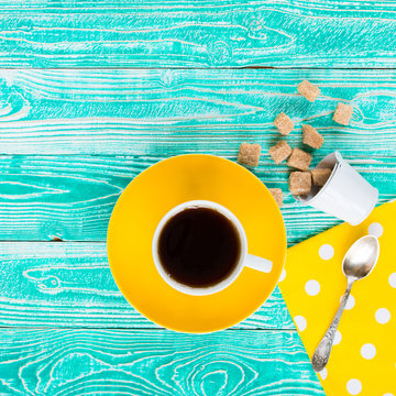cup of black tea, yellow plate  and sugar scattered from baby bucket on turquoise colored wooden table with yellow napkin at polka dots, top view