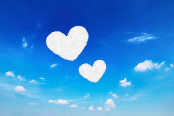 two heart shaped clouds on blue sky for valentine pattern and ba
