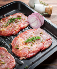 Raw fresh meat steak with rosemary leaves and salt on wood