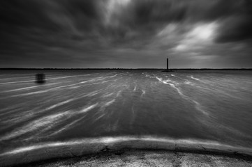 Landscape on the autumn coast. Lighthouse on the pier. Stormy weather. Long exposure shot. Black and white photo.