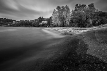 Landscape on the autumn coast. Stormy weather. Long exposure shot. Black and white photo.