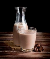 Glass of chocolate milk on wood table,dark background