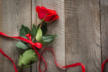 Valentine's card. Red rose with ribbon on wooden board. Top view.