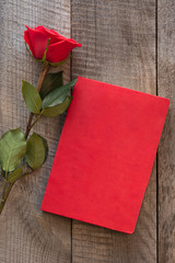 Valentine's card. Red rose and red notebook on wooden board. Top view.