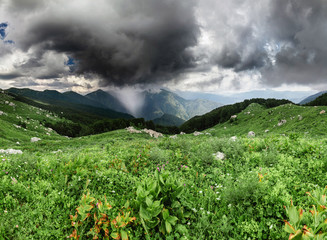 Panoramic landscape with passing rain storm clouds in the mountains