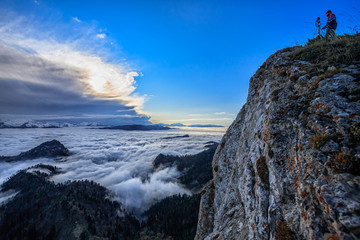 Beautiful scenic autumn mountain landscape at sunset with low clouds and a man standing on the rock and taking photos with a camera on a tripod. Wide angle scenery