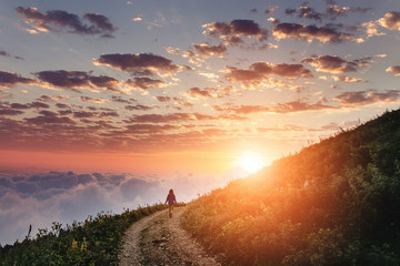 Woman on trail admiring the sunset with clouds and fog.