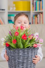 kleiner junge mit frühlingsblumen