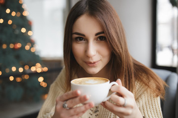 Lovely woman blowing on cup of coffee in a cafe