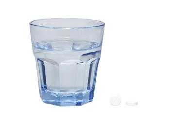 Zwei Tabletten und ein Glas Wasser, freigestellt