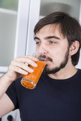 man making the juice from fresh vegetables and fruits in the kitchen