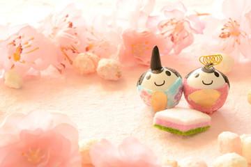 雛人形と雛あられ 桃色和紙背景