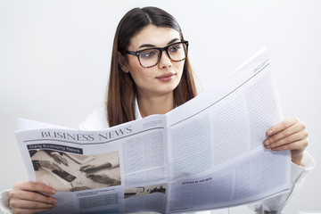 Businesswoman reading newspaper on gray background