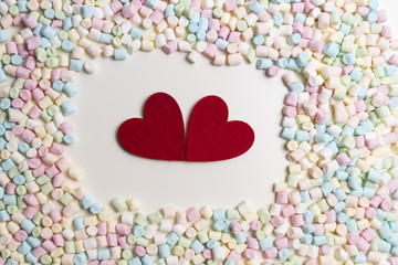 Two red hearts in the frame of colorful mini marshmallows as background