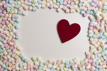 Red heart in the frame of colorful mini marshmallows as background. Top view