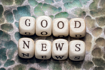 the word good news, lined with wooden blocks on a metal forged textural background.