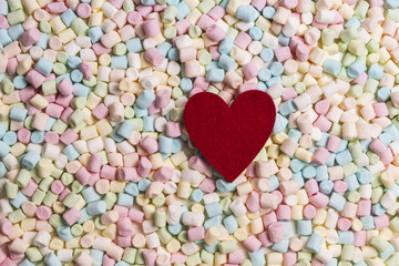 Red heart on colorful mini marshmallows background. Close up