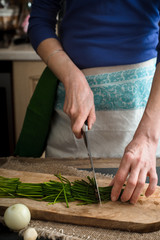Cutting spring onion on the wooden board vertical