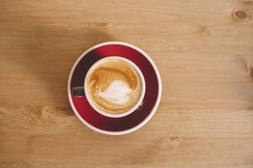 fresh morning cappuccino coffee in a grey cup with a red saucer on a wooden background