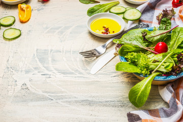 Healthy green salad preparation with dressing and cutlery on white rustic background. Diet eating, Vegetarian or vegan food concept