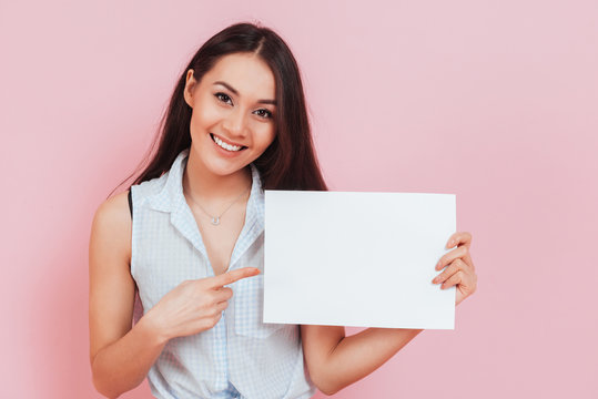 Young attractive woman holding blank billboard with copy space