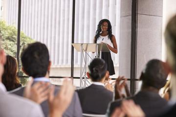 Audience at seminar applauding young black woman at lectern