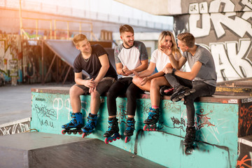 Young people on rollerblades sitting. Girl and guys in skatepark. Listen to the friend's story.