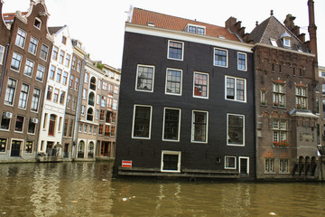 Vintage scene of Amsterdam traditional houses and water canals.