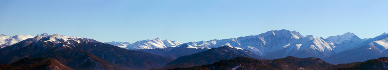 panoramic photo of the mountain peaks a Sunny winter day