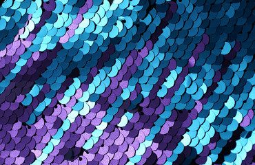 Sequins close-up macro. Abstract background with blue sequins and lilac color on the fabric. Texture scales of round sequins with color transition.