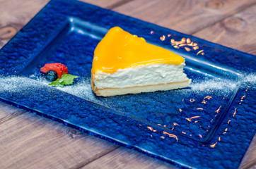 cheesecake with mango sauce, passion fruit on a blue background