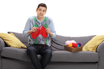 Confused young man attempting to knit